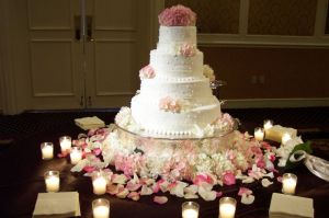 Round-wedding-cake-table-decorations-using-flowers-and-candle-votive